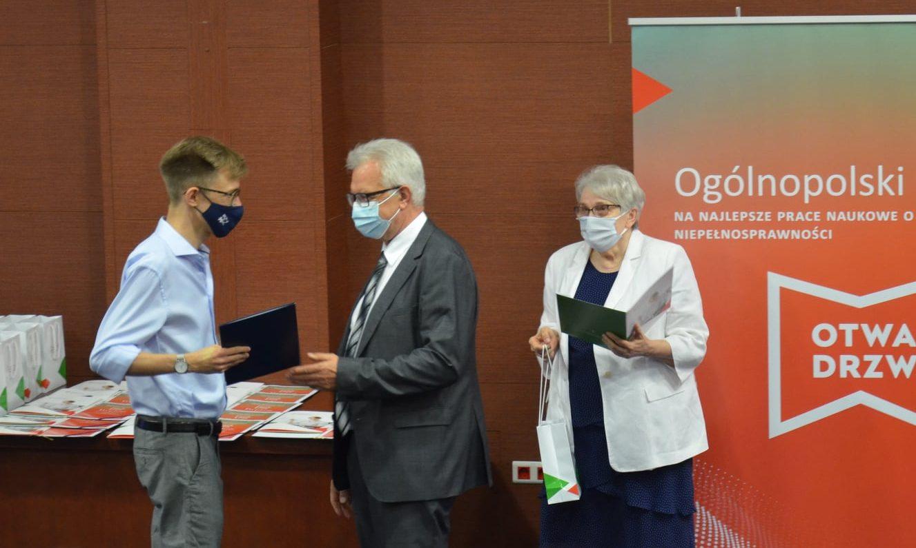 Dr Mateusz Płatos odbiera nagrodę z rąk prezesa zarządu PFRON